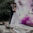 Married couple in tuxedo and dress standing on a rock by a stream with purple smoke behind them